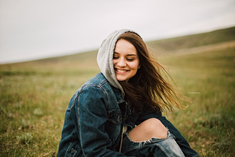 Smiling Long-hair Girl in a Hood Sitting in the Meadow