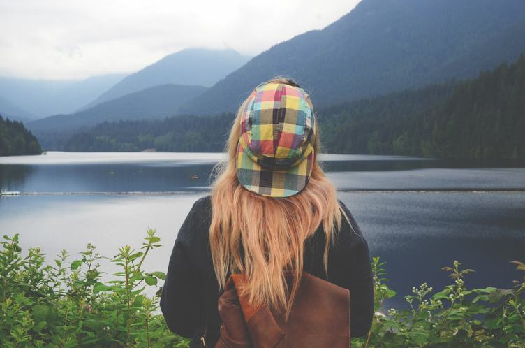 Girl with a Backpack Looking at a Mountain Lake