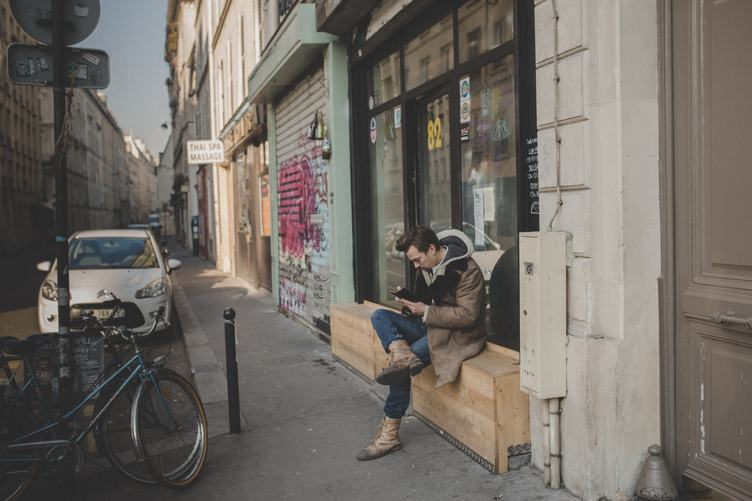 Sitting Man with his Smartphone in a Small Street