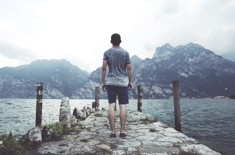 Young Man on a Stone Pier in front of a Mountain Lake