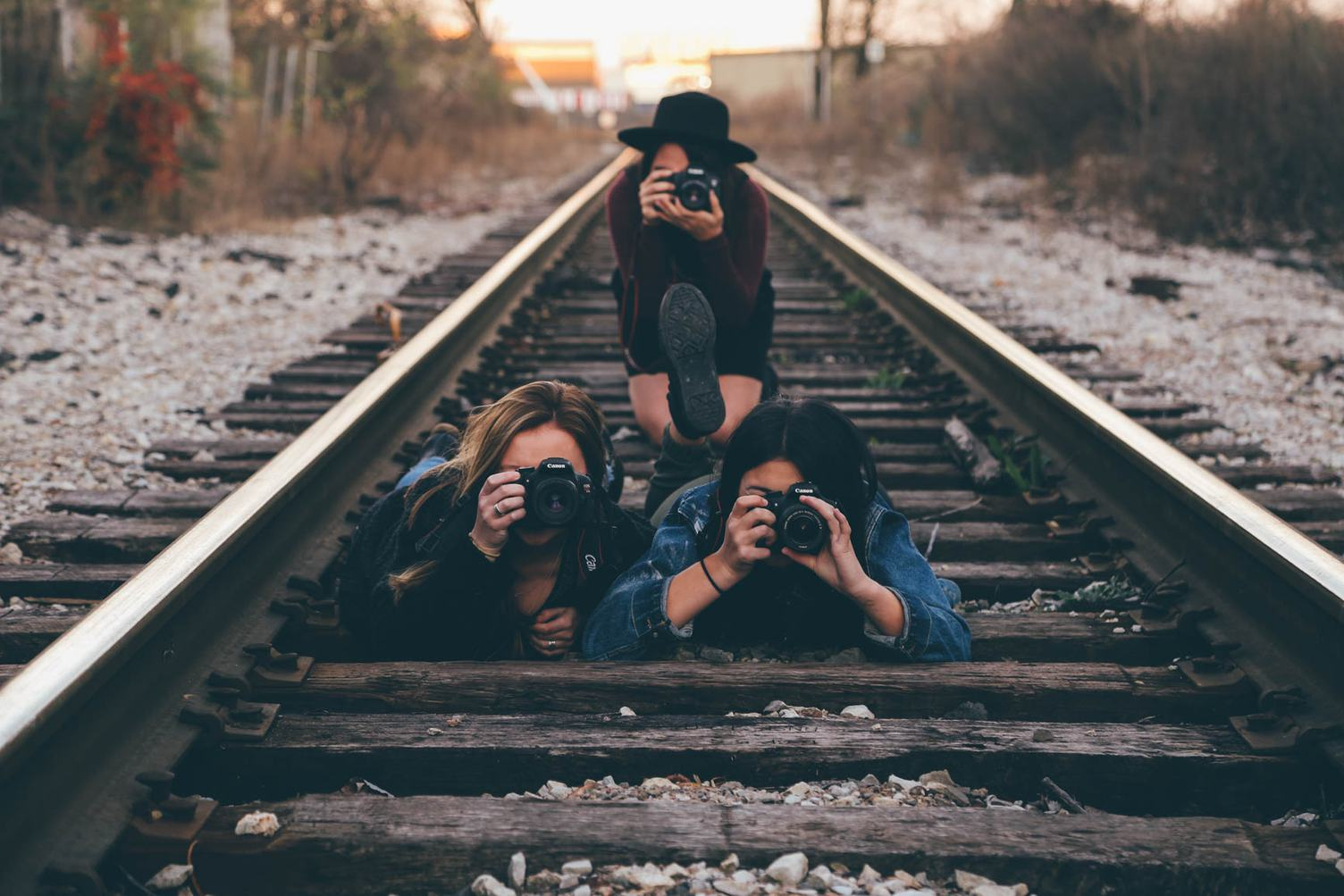 Three Young Girls Taking Pictures on Railroad Tracks