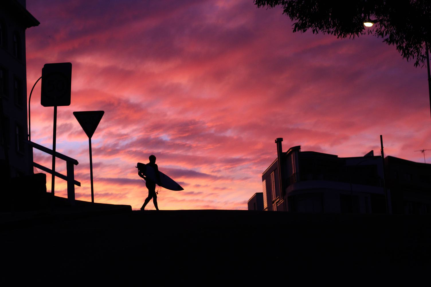 Silhouette of a Surfer against a Sunset Sky