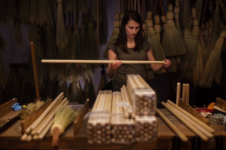 Young Woman Assembling Wooden Brooms