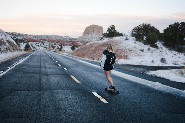 Blond Girl Skating on an Asphalt Road