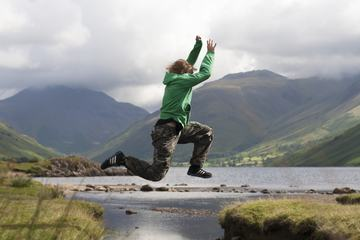 Young Boy Jumping Over the Mountains Lake Water