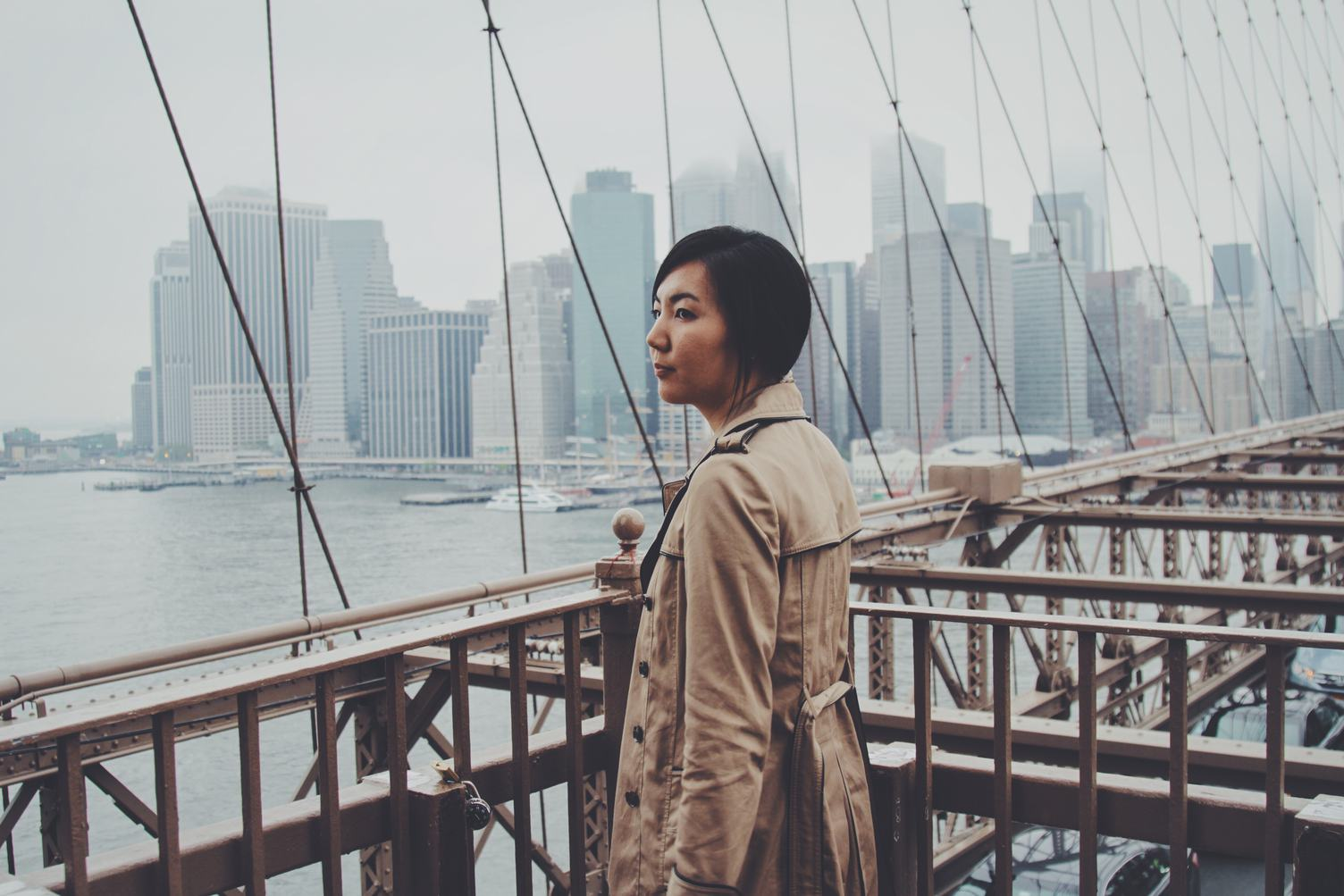 Woman wearing a Trench Coat standing on Brooklyn Bridge, New York