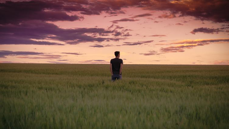 Young Man Walking on Field and Enjoying Sunset