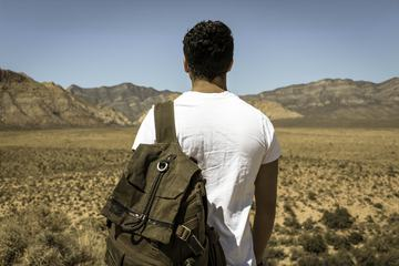 Young Man Alone with a Travel Backpack in a Desert