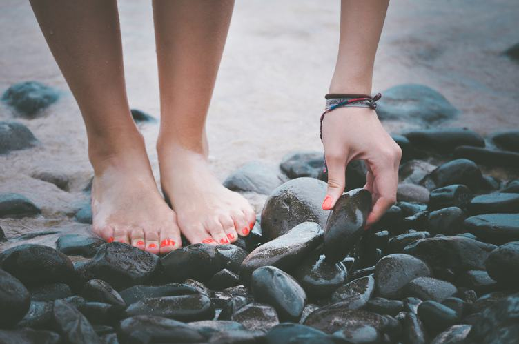 Barefoot Woman Standing on the Sea Pebbles