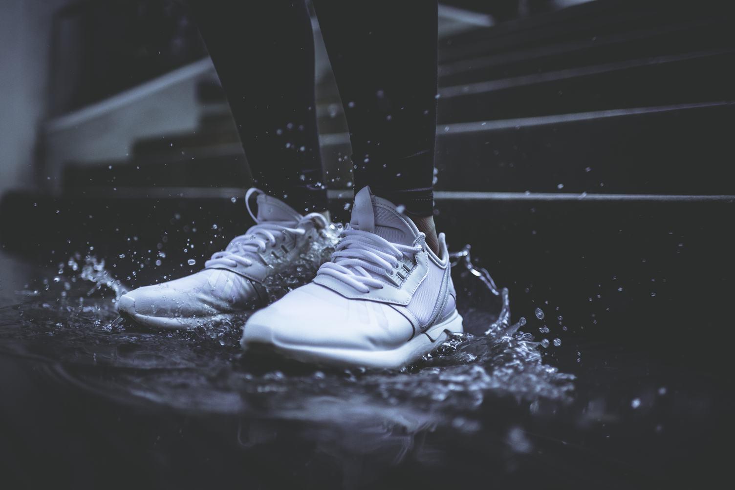 White Sneakers Splashing in Puddle