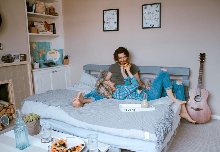 Couple Feeding each other in Bed with Pizza