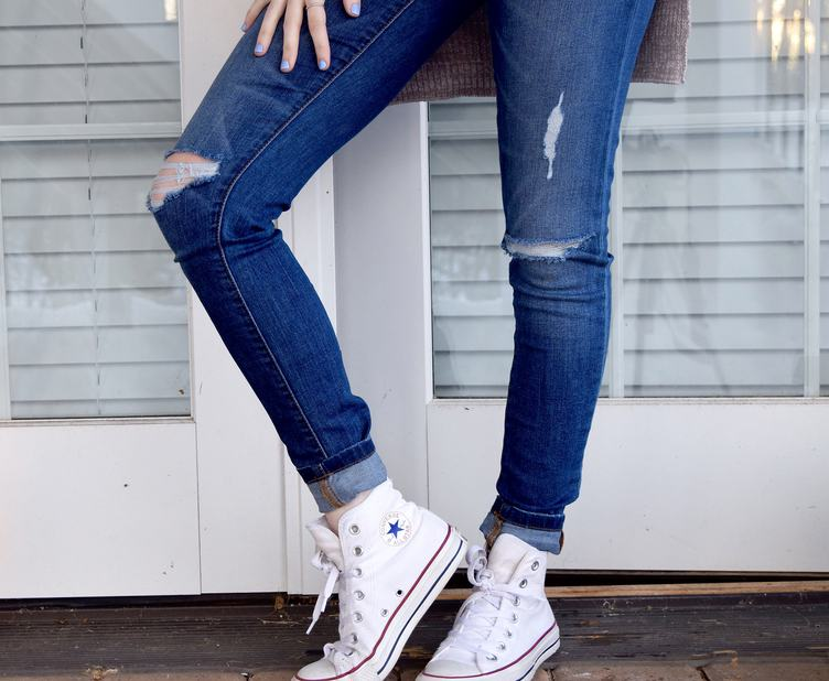 Woman Posing in Ripped Jeans against White Door