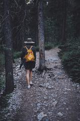 Hiker Woman with Backpack Walking on Path Forest