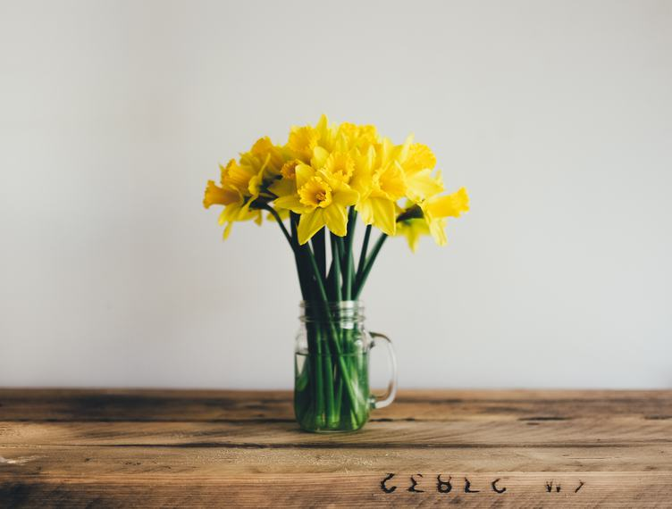Bunch of Yellow Daffodils in a Glass Vase on a Wooden Table