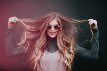 Smiling Woman in Sunglasses with Long Hair