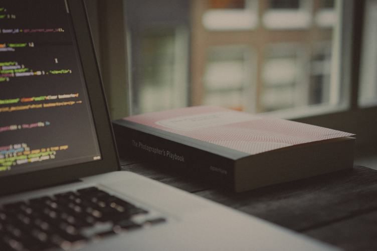 Laptop with Code Source on Photographer's Desk