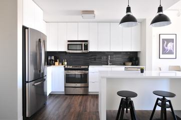 White Open Kitchen with Island, Fitted Cabinets and Black Stools