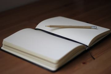 Blank Notebook with Pencil on Desk Background