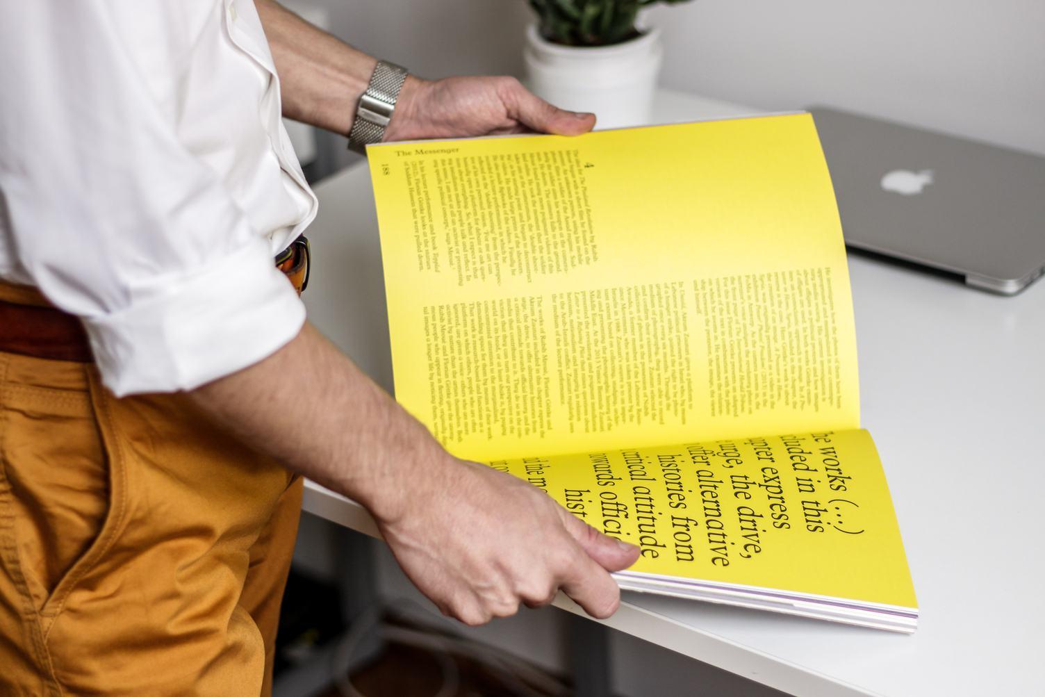 Man Reading a Magazine on a Desk Background
