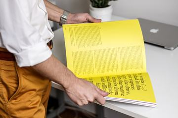 Man Reading a Magazine on a Desk Background