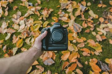 Holding a DSLR Camera with Autumn Colored Leaves in the Background