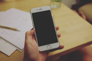 Hand Holding a Smartphone on Wooden Office Desk as a Background