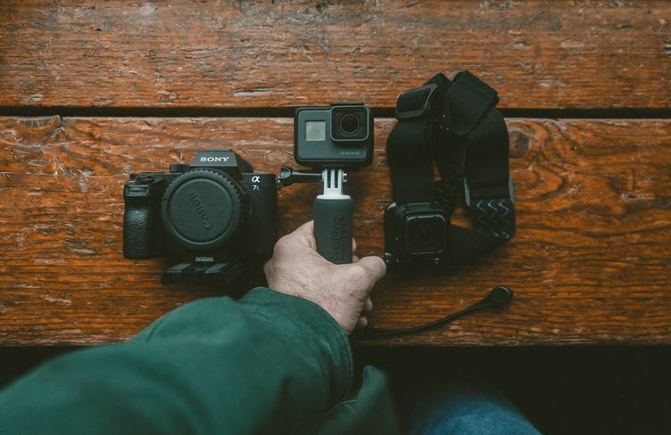 Man Holds Small Action Camera on Wooden Background