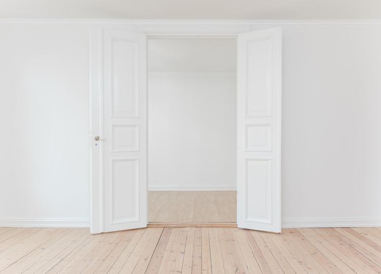 White Door in Empty Apartment Room with Wooden Floor