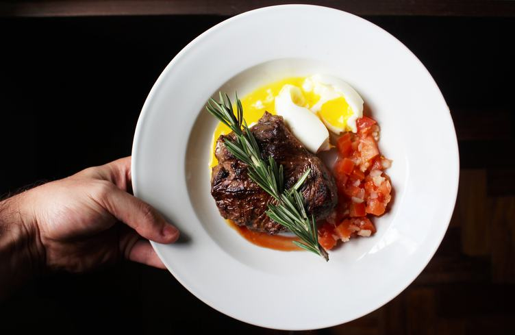 Steak with Tomatoes and Soft-Boiled Egg on the White Plate
