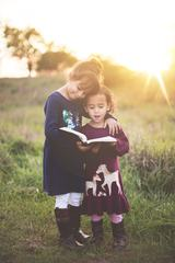 Happy Sisters Hugging with Love and Reading Book Together