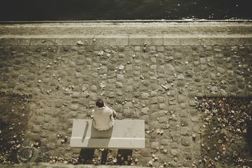Man Sitting on a Bench at the River Bank of Seine