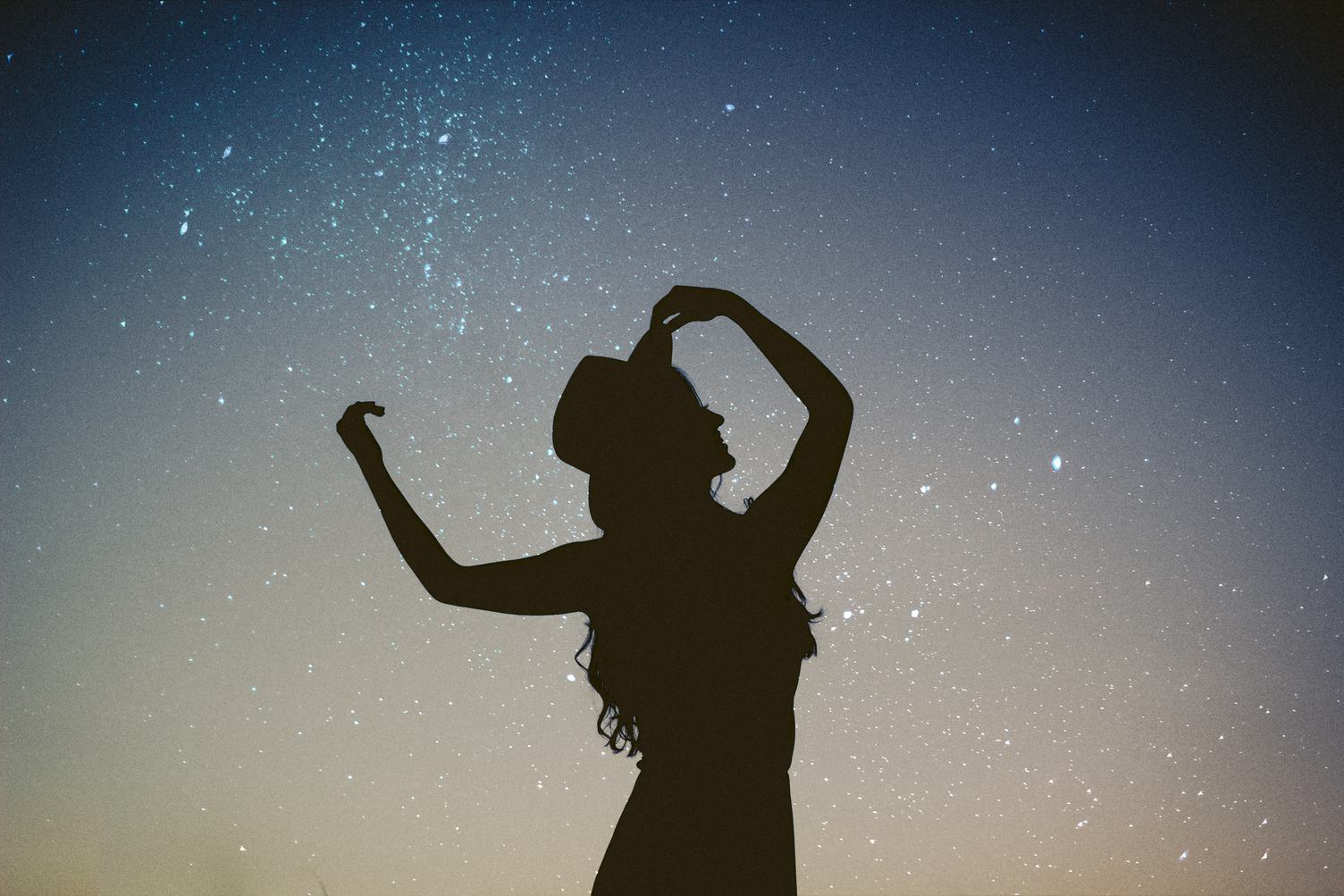 Silhouette of a Woman Standing Outside, Starry Night Background