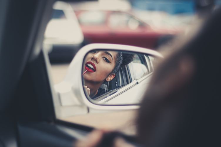 Woman Applying Lipstick in a Car, Mirror Reflection