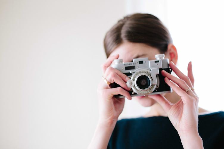 Woman with Vintage Camera in the Hands