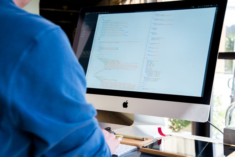 Programmer Working Writing Code at His iMac