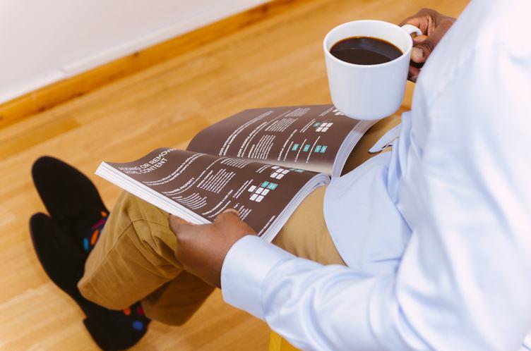 Businessman Reading Magazine and Drinking Coffee