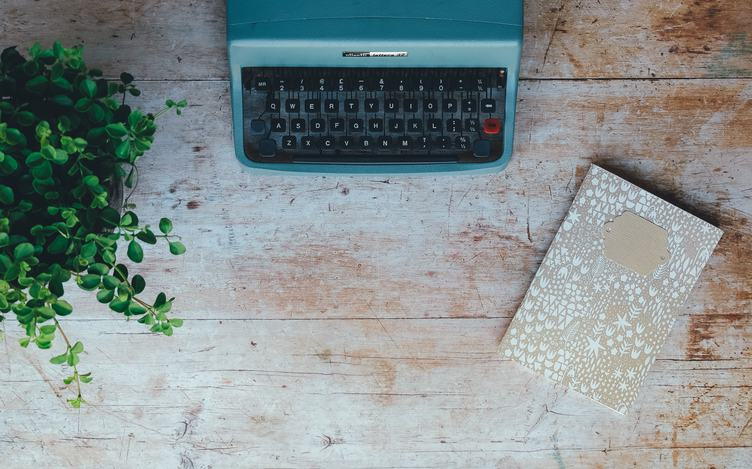 Blue Vintage Typewriter with Plant and Notebook on the Grung Wooden Table