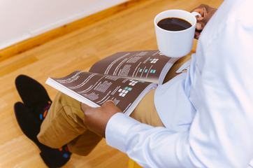 Businessman Reading Magazine and Drinking Coffee