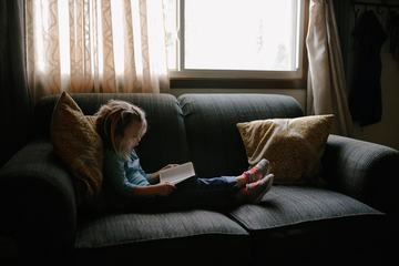 Young Girl Reading a Book and Sitting on Sofa at Home