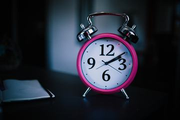 Pink Alarm Clock on Dark Background
