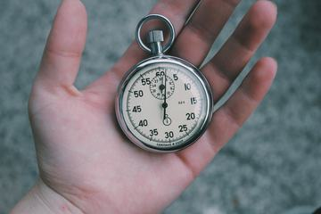 Close Up of Hand Holding Stopwatch Outdoors