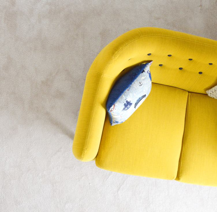 Yellow Sofa with Pillow on Beige Carpet Background