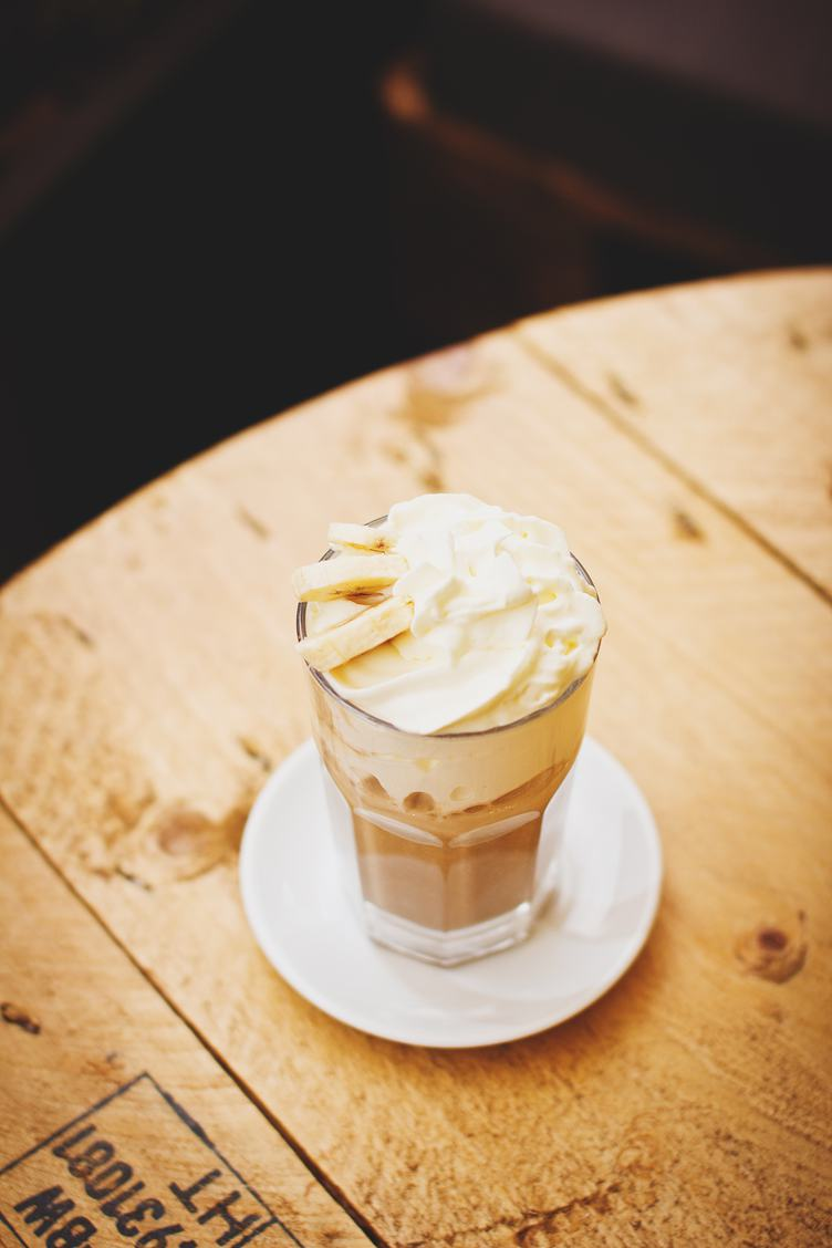 Coffee with Cream and Bananas on Wooden Table