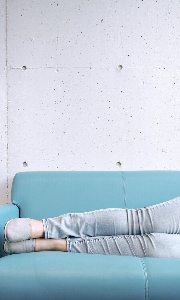 Legs of Young Woman Lying on Blue Sofa against Concrete Wall