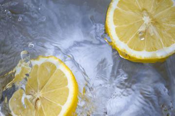 Sliced Lemons Falling Into Water
