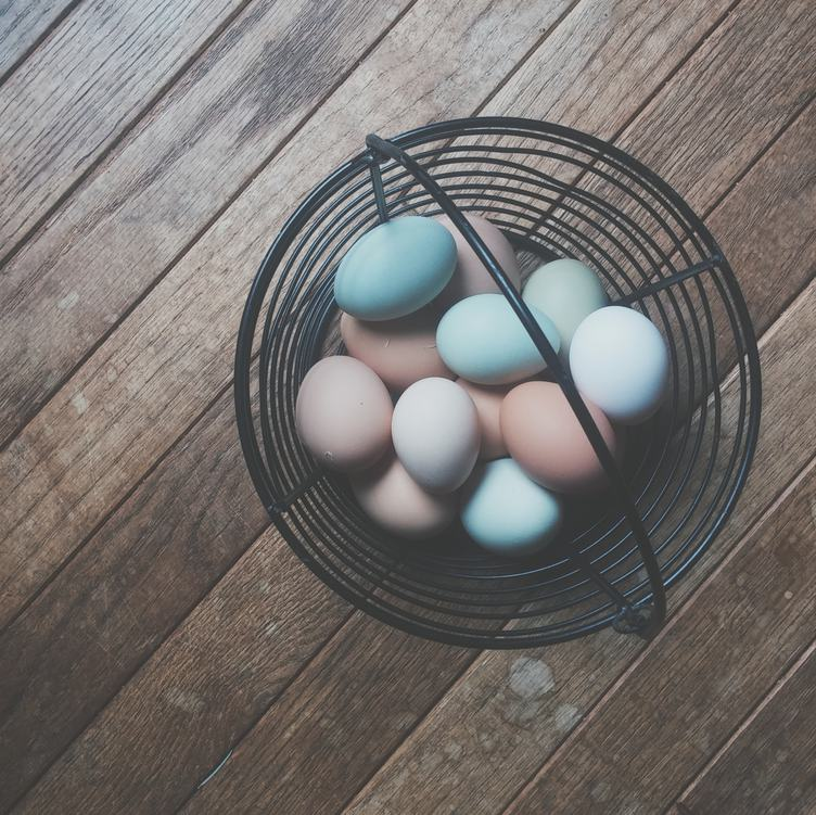 Colored Easter Eggs in Black Wire Basket on Wooden Floor