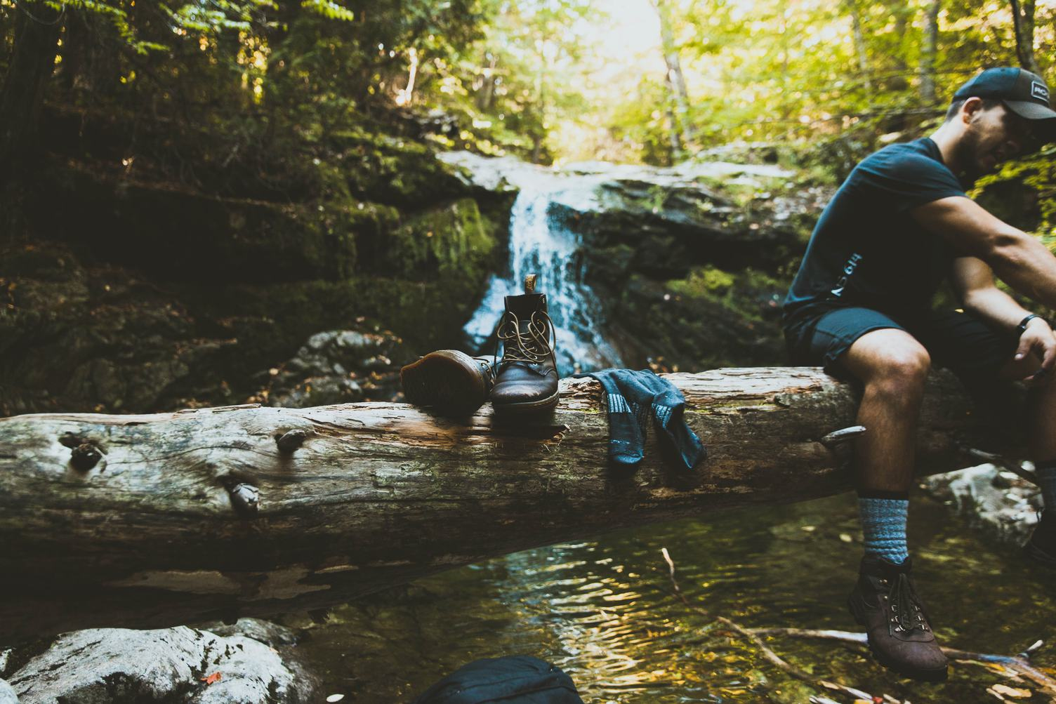 Hiker High Boots and Socks on a Fallen Log at the Mountain Stream