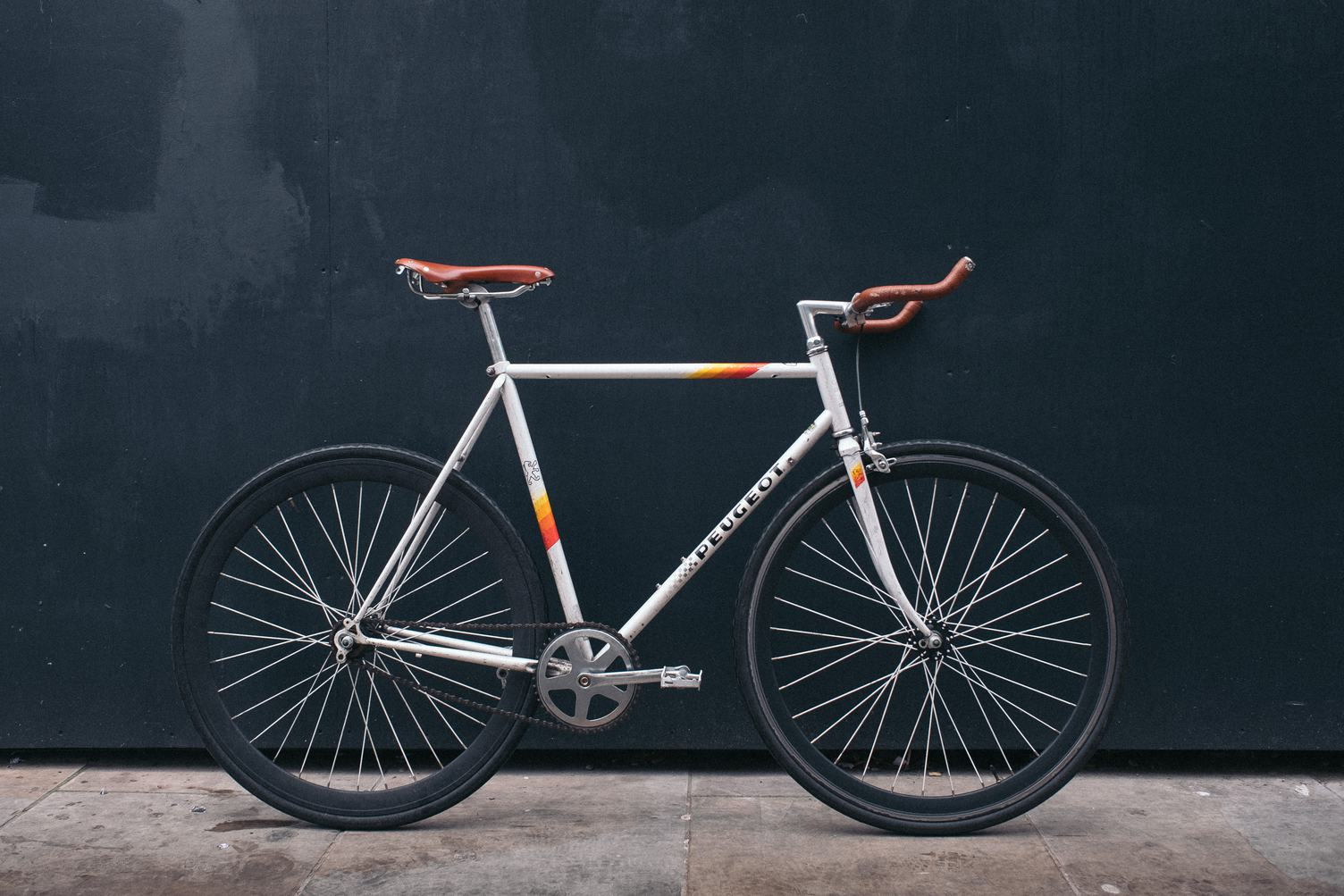 White Peugeot Bike Leaning on a Black Wall