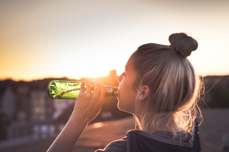 Girl Drinking a Beer at the Sunset