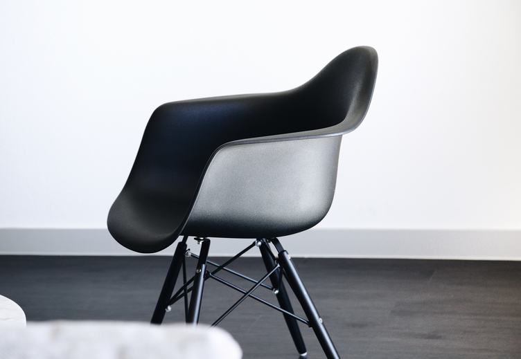 Modern Black Chair in White Room Interior with a Dark Floor